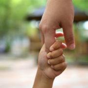 Eine Erwachsenenhand und eine Kinderhand, die sich halten.